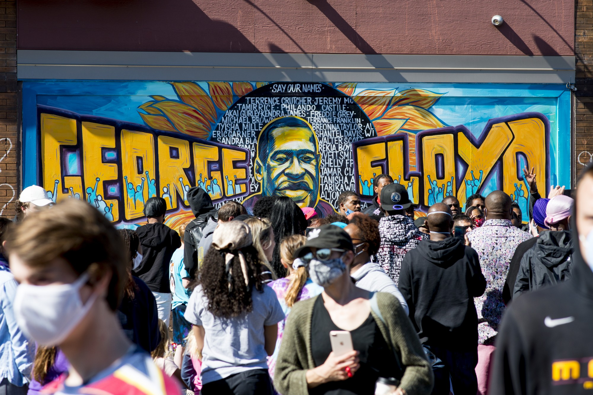 Demonstrators gather near the intersection of Chicago Avenue and East 38th Street at a memorial established for George Floyd on Friday, May 29.