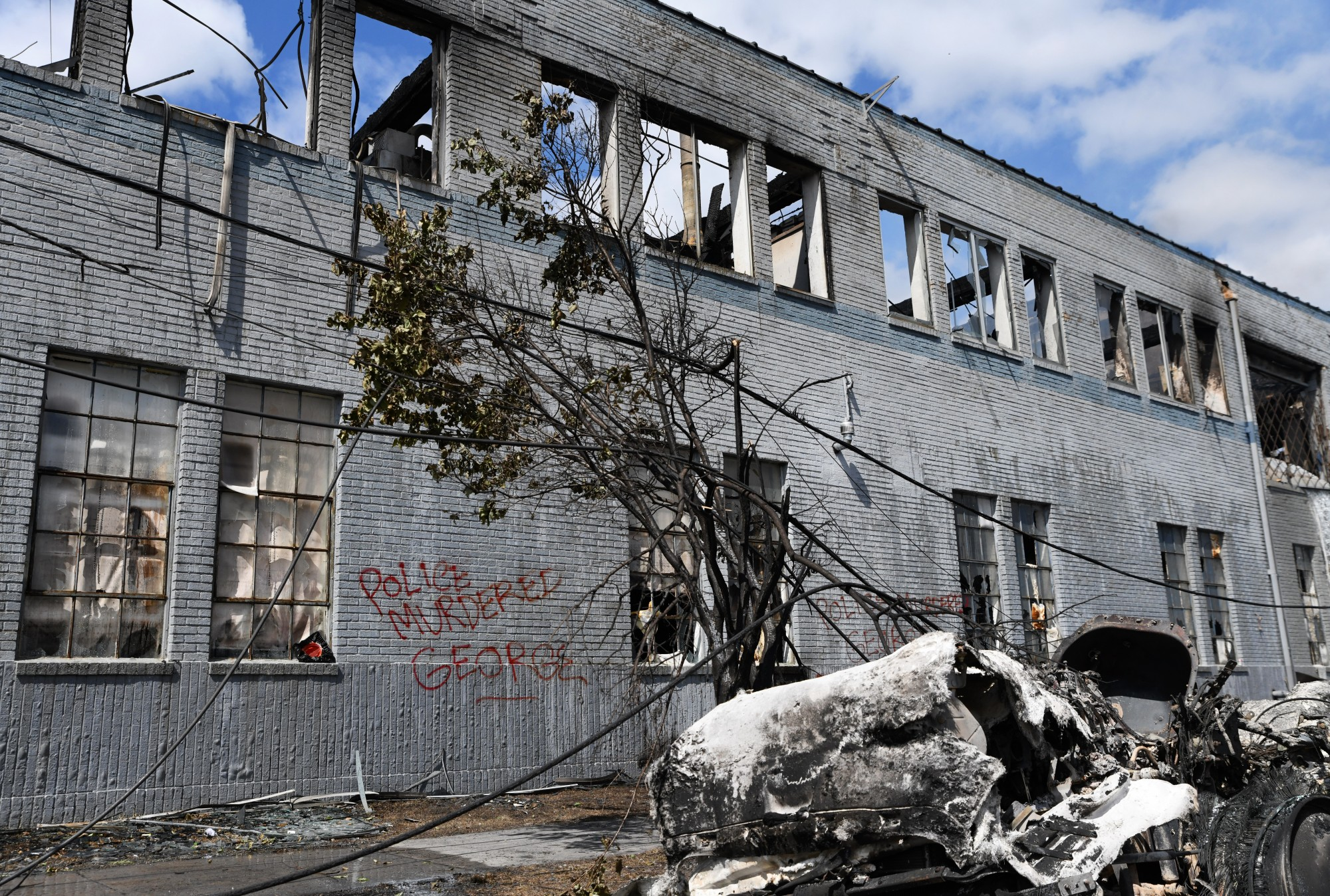 """""""Police Murdered George"""" is spray-painted on the wall of a burned building next to a melted vehicle and downed powerline near the MPD 3rd Precinct in Minneapolis on Friday, May 29."""
