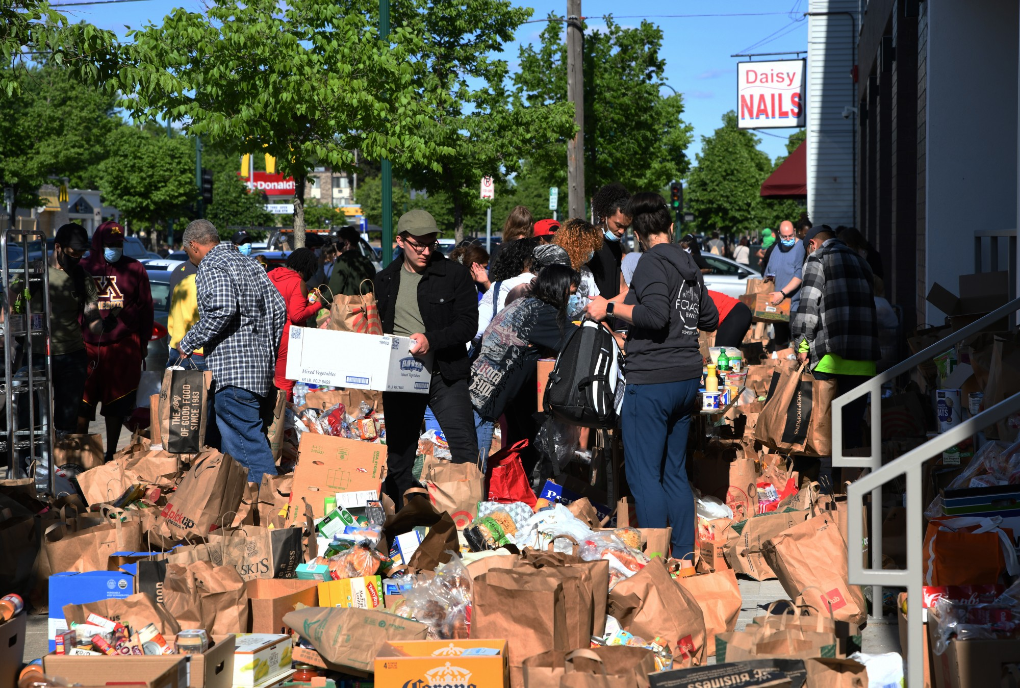 People drop off donations and take what they need from an impromptu community food shelf in front of Minnehaha Commons on East Lake Street near the Minneapolis 3rd Police Precinct on Friday, May 29.