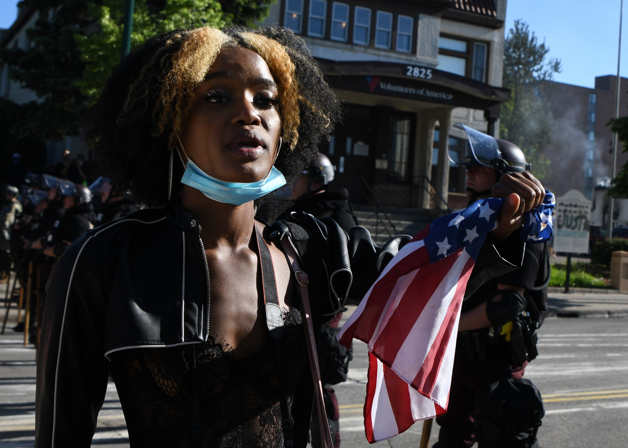 """Akilha Venzant holds an American flag while addressing law enforcement in front of demonstrators on E Lake Street near the MPD 3rd Precinct in Minneapolis on Friday, May 29. While the crowd of demonstrators chanted """"Black Lives Matter"""", Venzant walked along the line addressing each officer, saying """"Black lives matter. They do. They really do."""""""