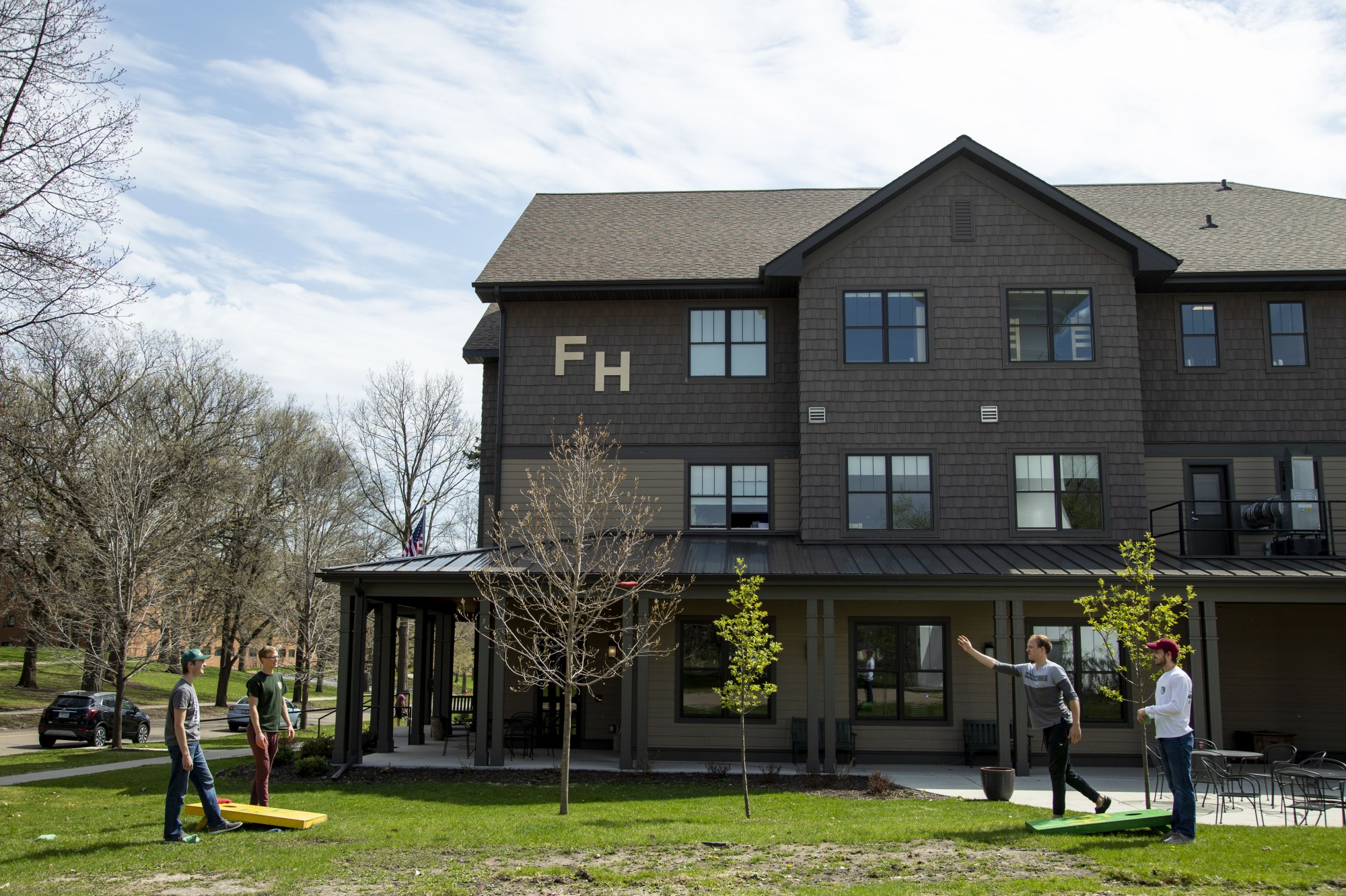 3:15 p.m. Members of the FarmHouse fraternity play a game of bags.