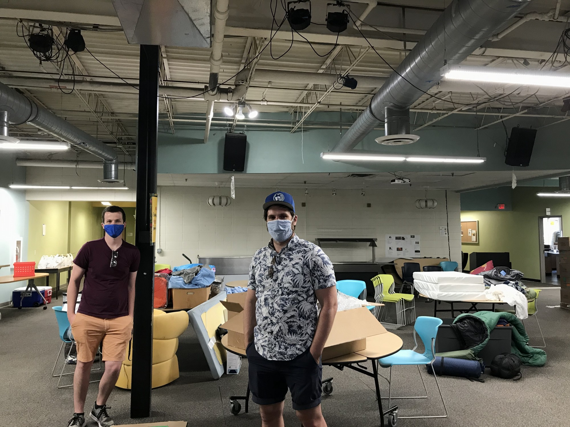 <p>Mike Buttgereit, left, and Michael Warner, right, stand for a portrait in a central hall at Venture Academy on Saturday evening. The public charter school is open over the weekend as a shelter for families seeking refuge from protests and unrest.</p>