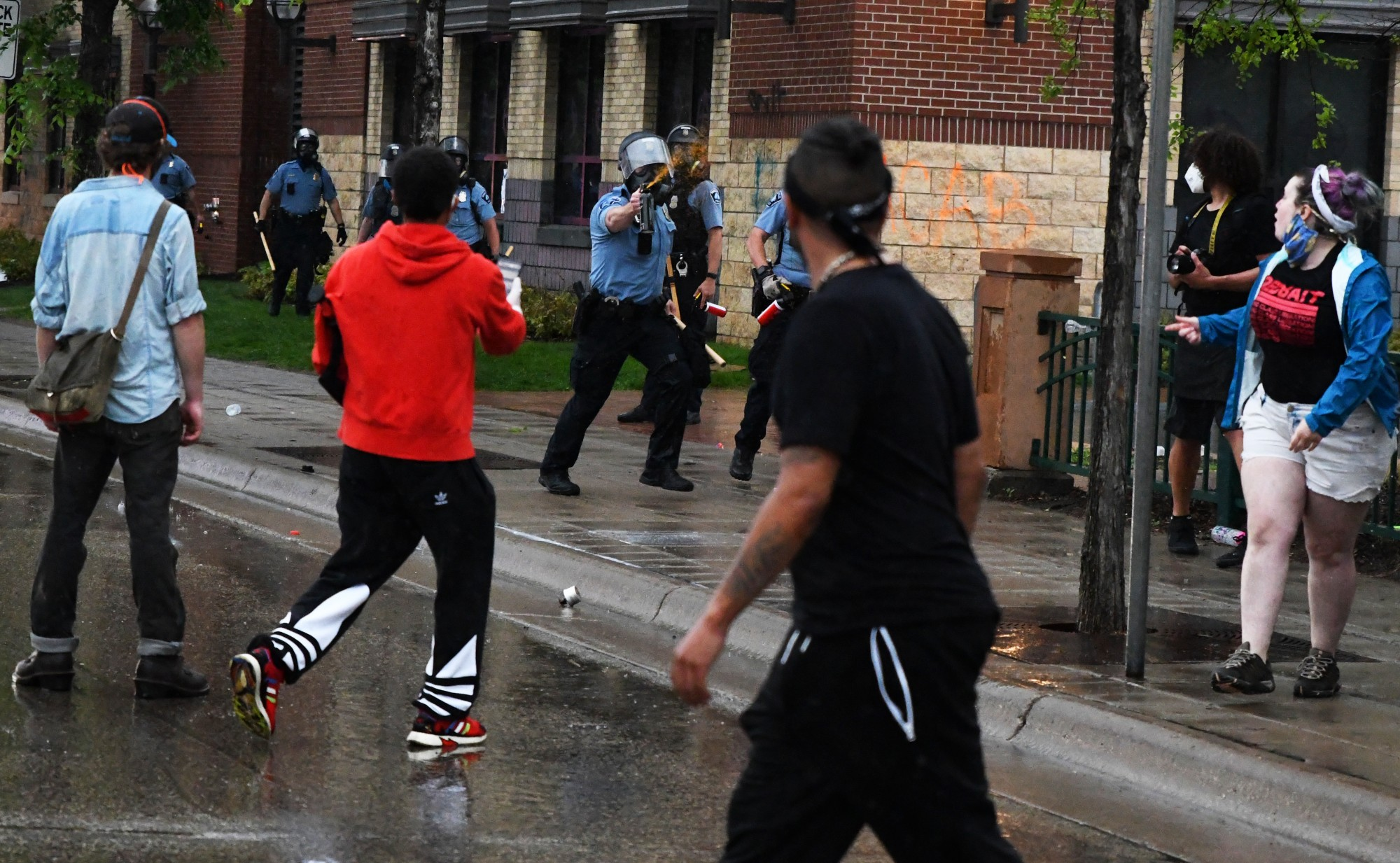 <p>A police officer pepper sprays a demonstrator while running after them outside of the Minneapolis 3rd Police Precinct on Minnehaha Avenue on Tuesday, May 26.</p>