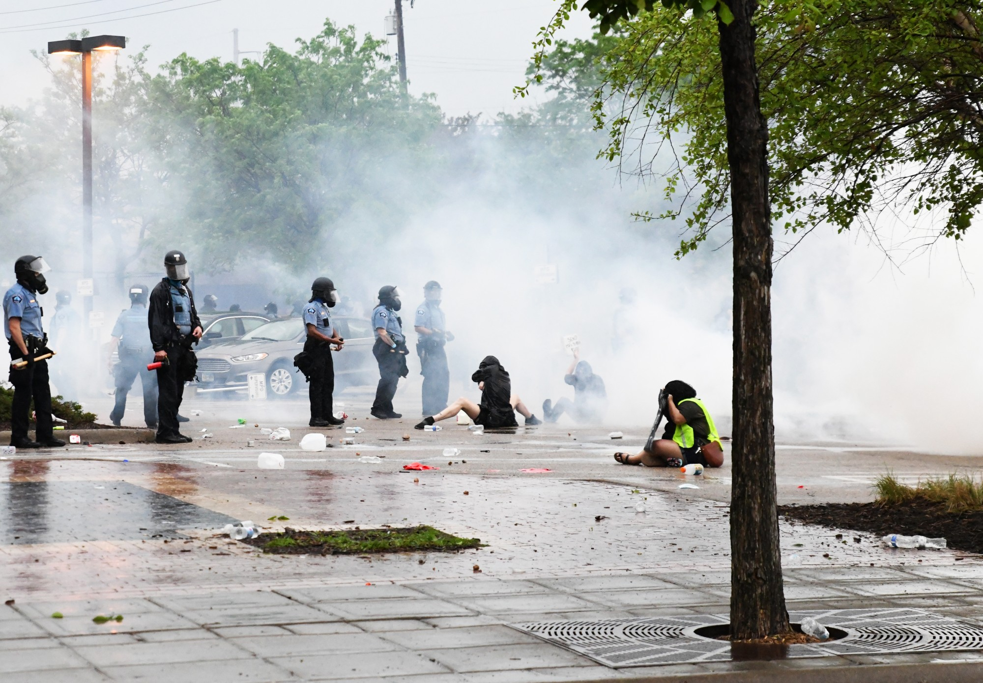 Protesters sit in clouds of tear gas outside of the Minneapolis 3rd Police Precinct on Minnehaha Avenue on Tuesday, May 26.