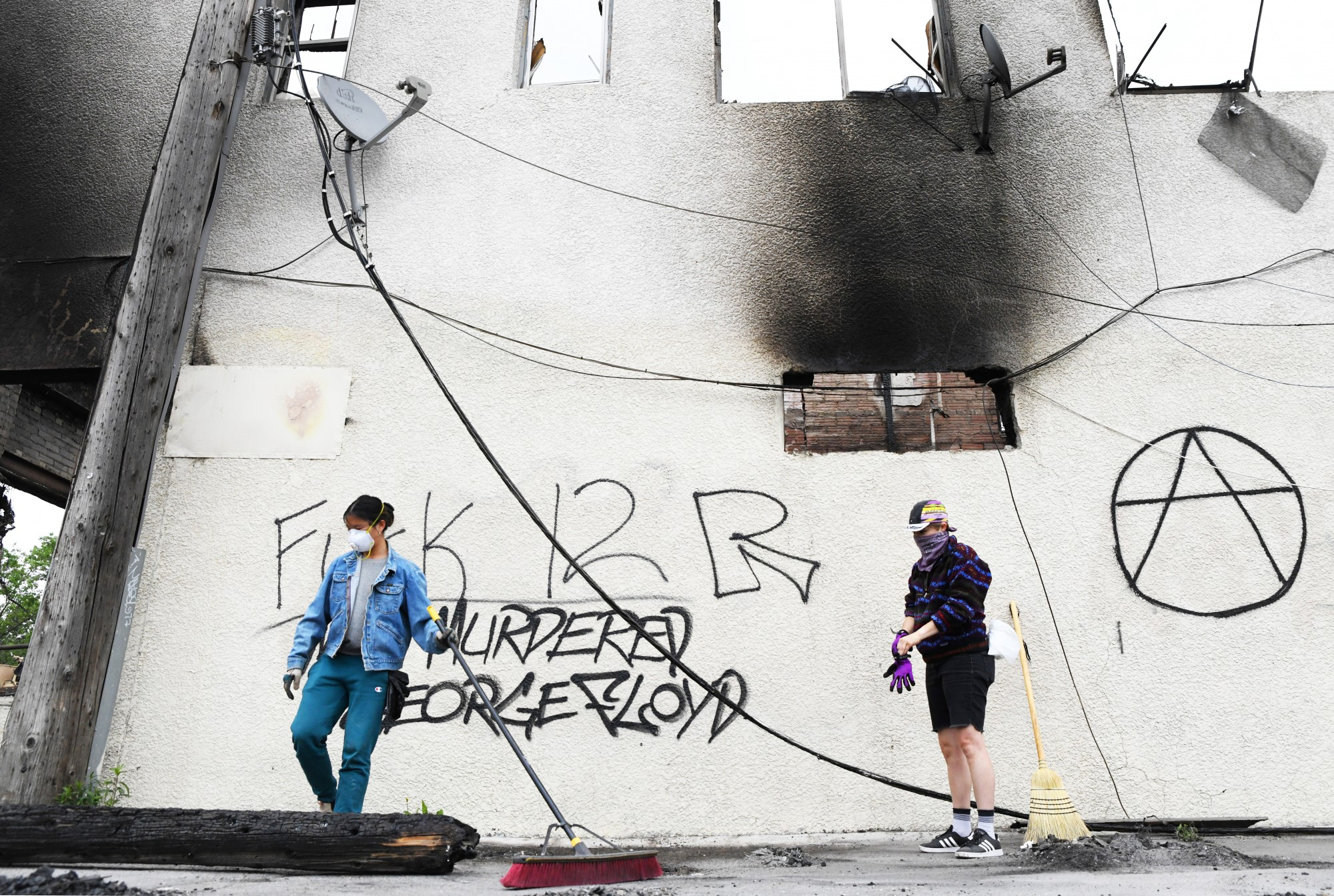 Ellen Vanden Branden, left, and Erin Horvath, right, sweep charred wood, broken glass and other debris outside of a burnt-out building on East Lake Street in Minneapolis on Friday, May 29. Vanden Branden and Horvath both have strong ties to the neighborhood and voluntarily showed up to help.