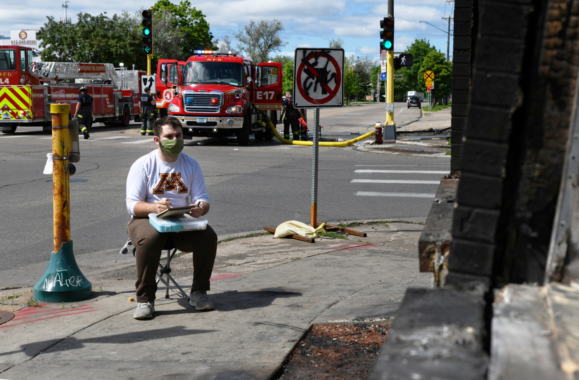 """Austin Kedrowski sketches the burnt-out Domino's Pizza on 26th Avenue South near the Minneapolis 3rd Police Precinct on Friday, May 29. Kedrwoski said, """"I believe there is a need for documentation beyond what photos can share, so I draw."""""""