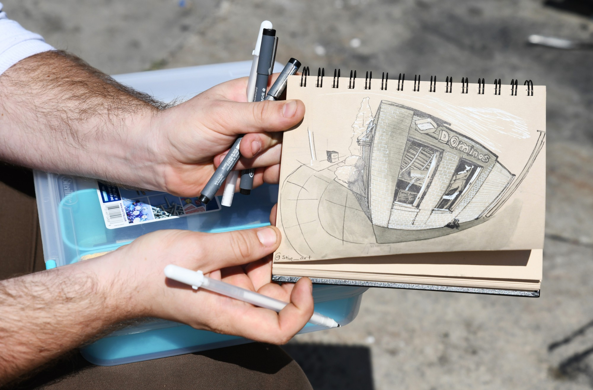 Austin Kedrowski shows his sketch of the burnt-out Domino's Pizza on 26th Avenue South near the Minneapolis Police Department 3rd Precinct on Friday, May 29.