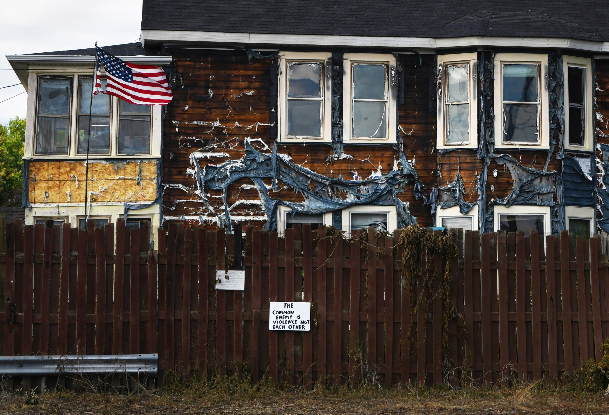 An American flag flies outside of a residence with melted siding along East 29th Street near the Minneapolis 3rd Police Precinct on Friday, May 29, while a sign on the exterior fence reads,