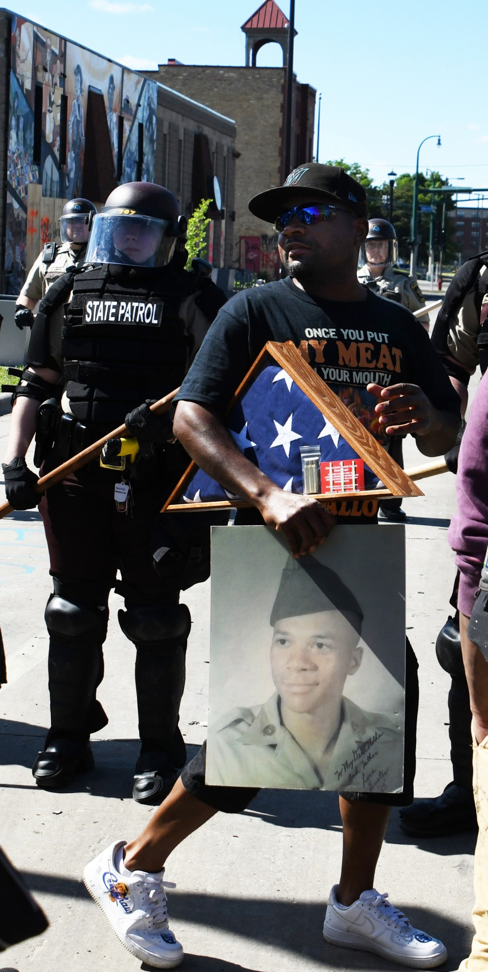 """Bernard Duckworth Jr. carries his father and U.S. Armed Forces Veteran Bernard Duckworth's flag and portrait while addressing the assembled demonstrators and law enforcement near the Minneapolis 3rd Police Precinct on Friday, May 29. """"We have soldiers on the front lines for real … including in hospitals … and they are dying for America,"""" Duckworth said. """"All these people out there [at the protest] are Americans, and on the other side are more Americans."""""""