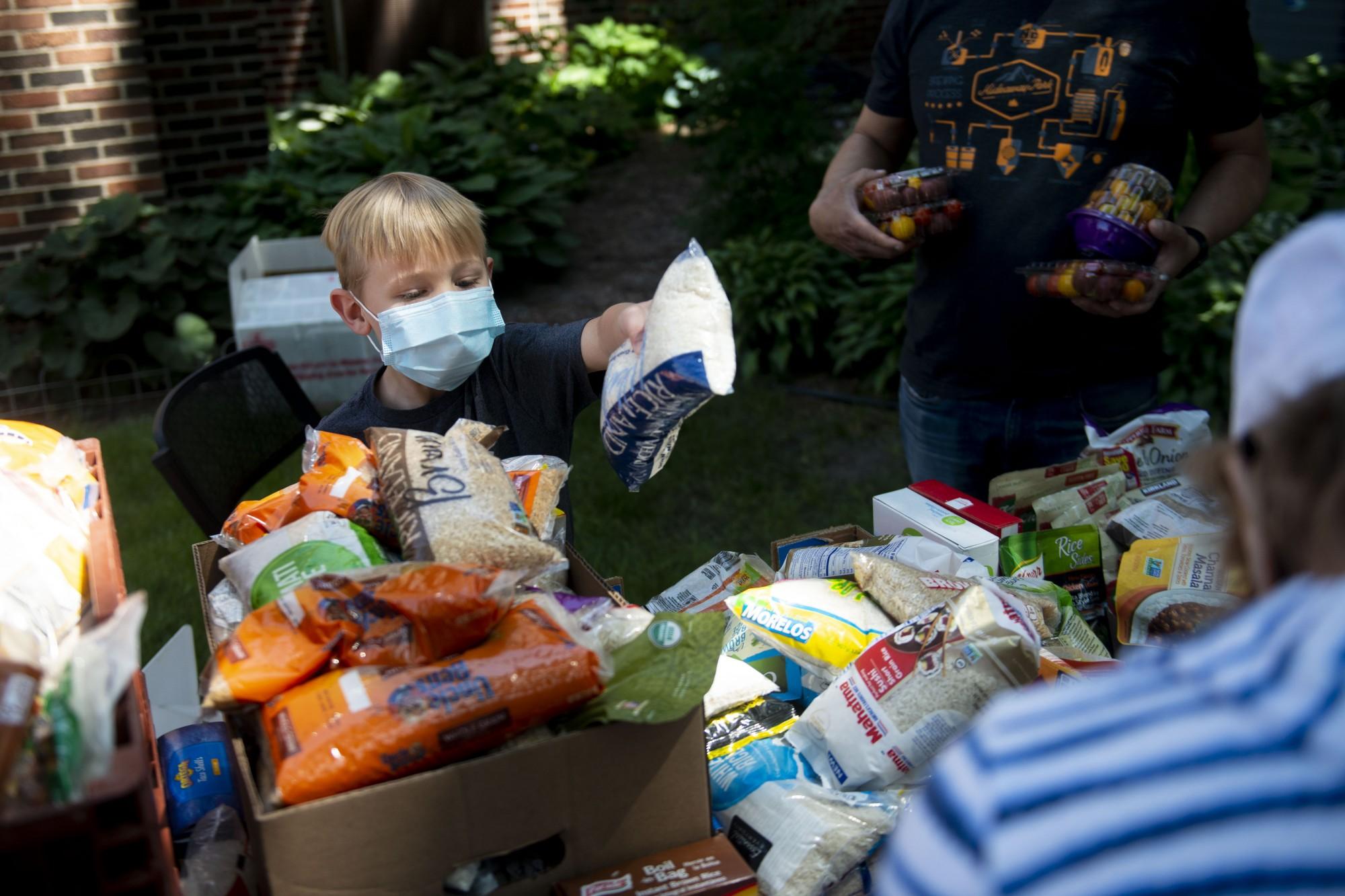 Luca Maki (7) helps organize donated rice at Holy Trinity Lutheran Church on Sunday, May 31.