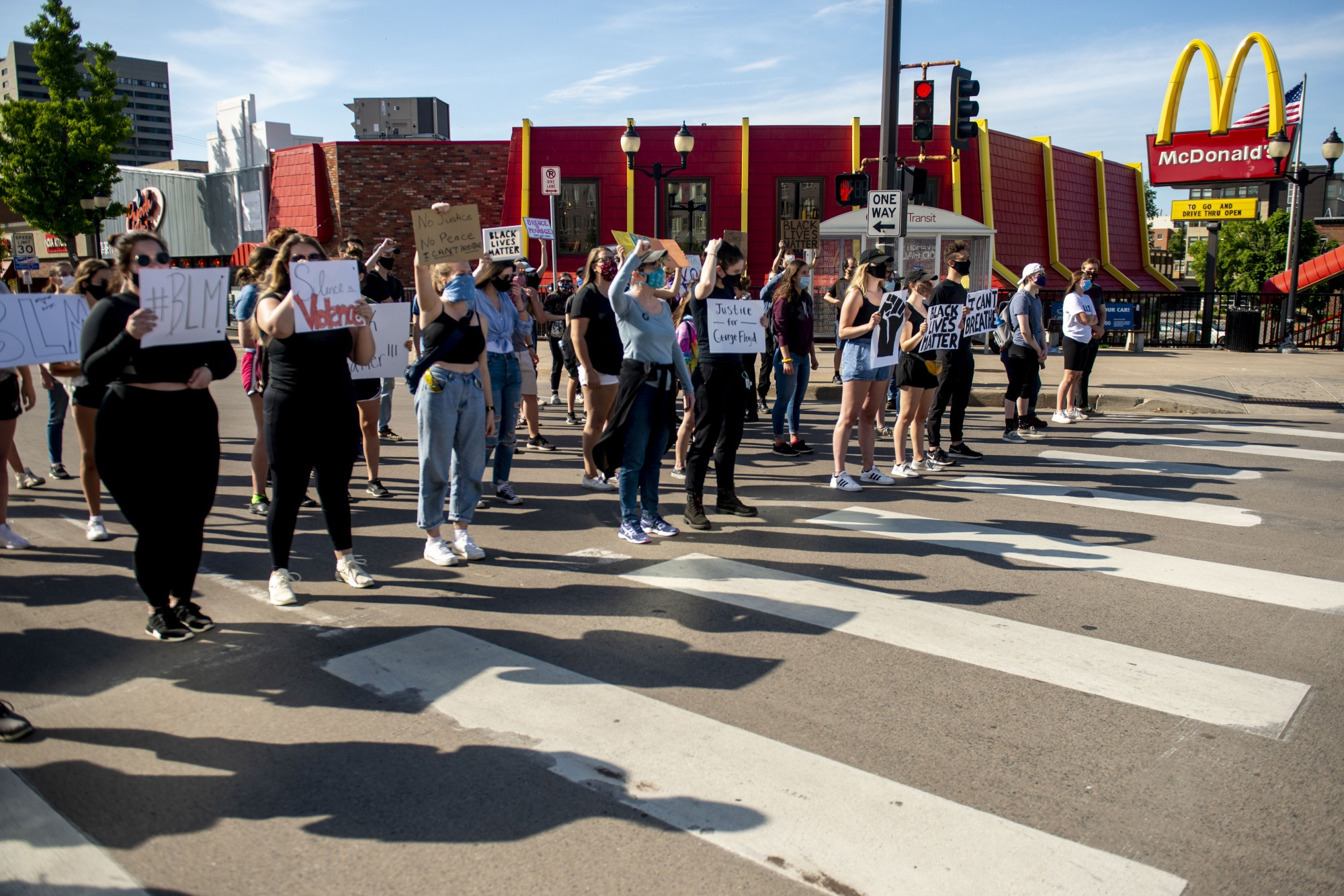 Students protest at the entrance of Dinkytown blocking traffic from passing through on SE 4th St on Sunday, May 31. Cars passing by frequently honked in support of the crowd.