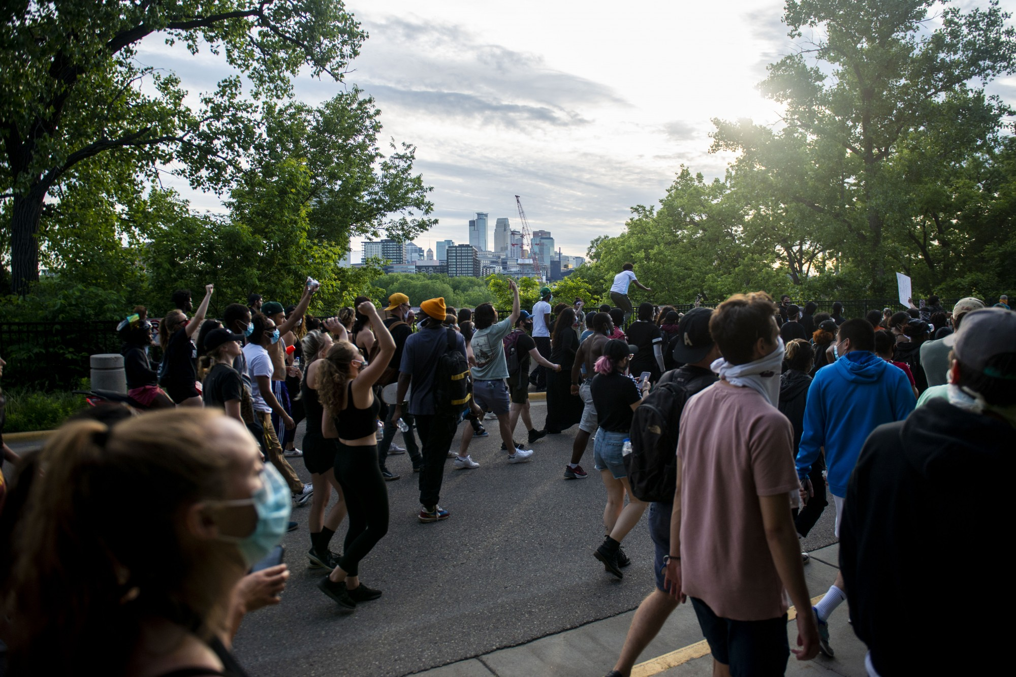 Demonstrators make their way through parts of campus as curfew nears, eventually crossing the Stone Arch Bridge and into downtown on Sunday, May 31. (Jack Rodgers / Minnesota Daily)