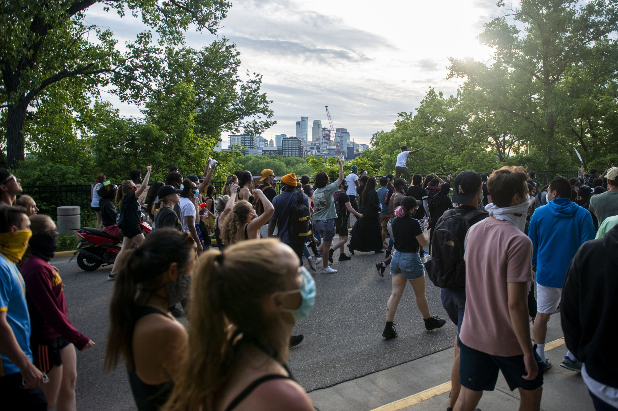 Demonstrators make their way through parts of campus as curfew nears, eventually crossing the Stone Arch Bridge and into downtown on Sunday, May 31.
