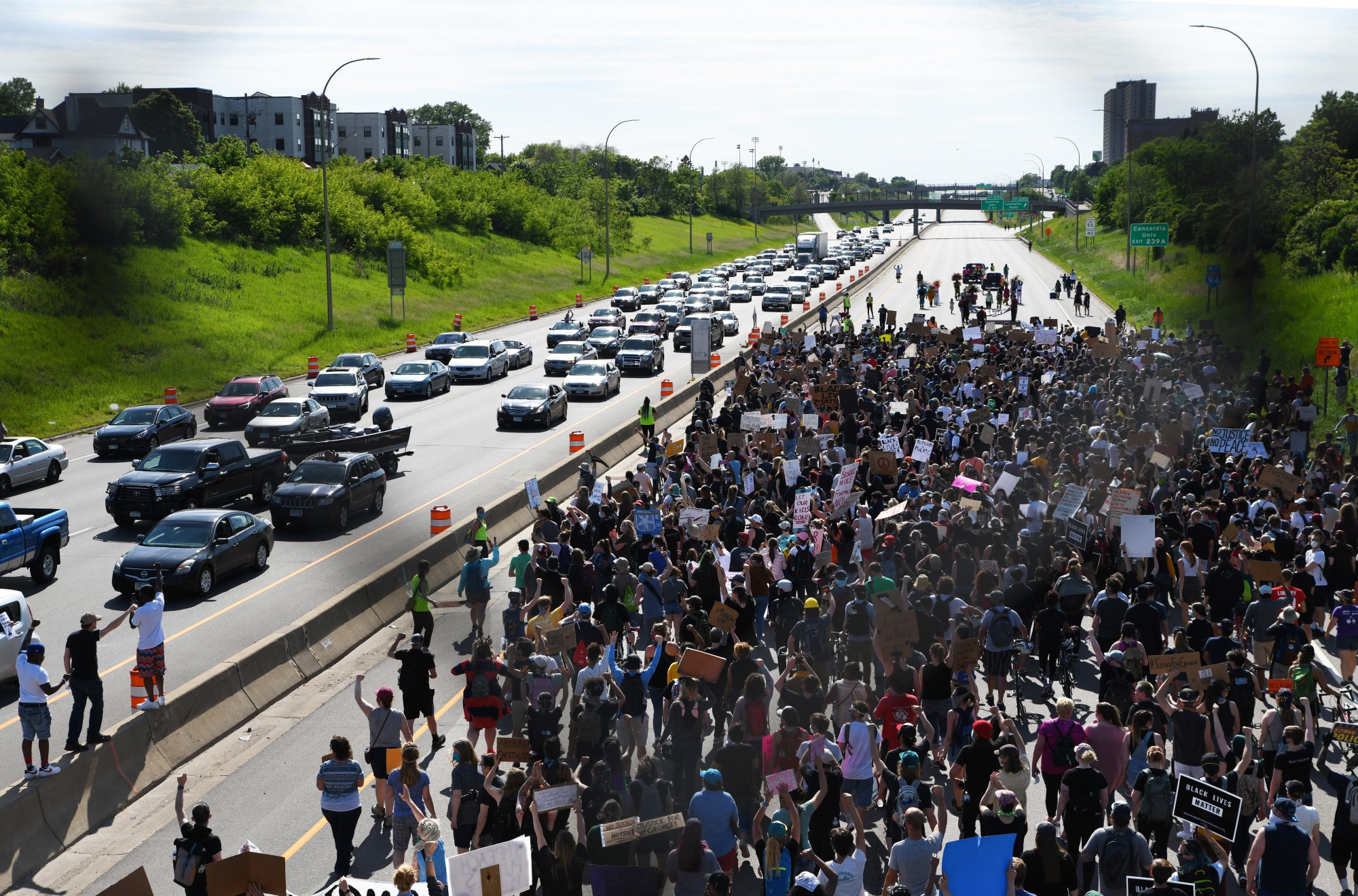 Eastbound traffic on I-94 slows to a halt as drivers raise their fists, honk in support or film demonstrators in the westbound lane on Sunday, May 31 in St. Paul.