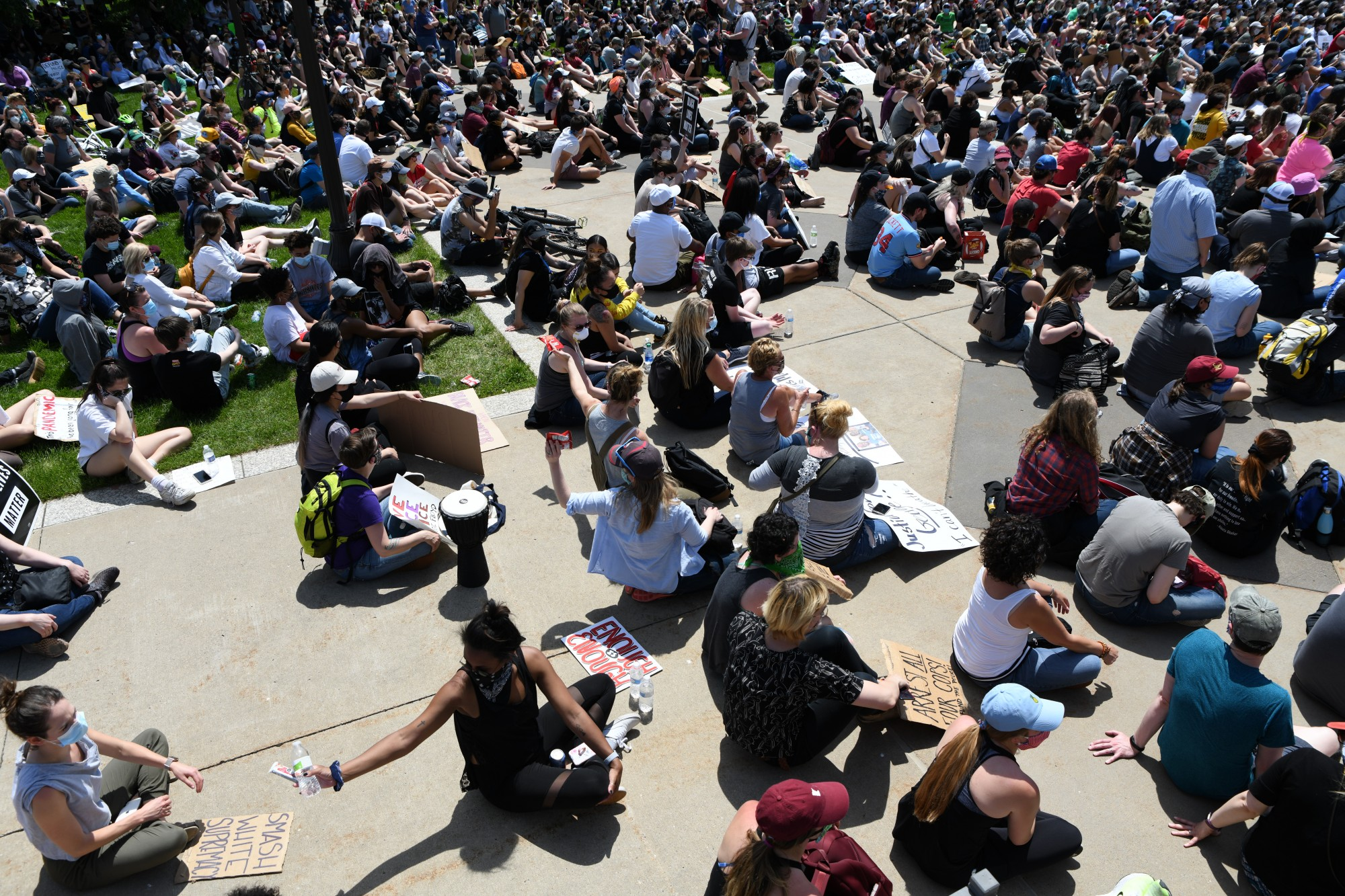Demonstrators distribute bottled water and snacks through the crowd as they sit in front of the Minnesota State Capitol on Sunday, May 31.