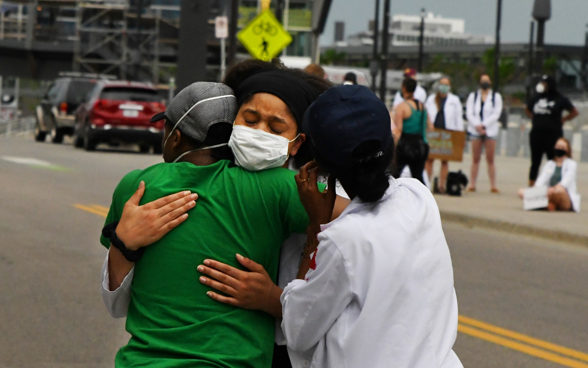 Dominique Earland hugs fellow University of Minnesota medical students after addressing the crowd of medical students and professionals outside of the Hennepin County Medical Examiner's office on Tuesday, June 2.