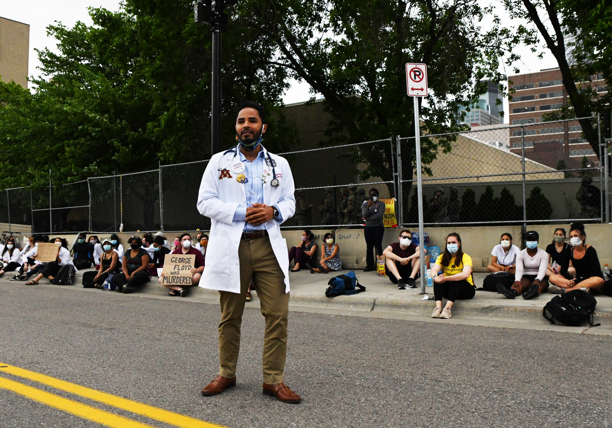 """University of Minnesota internal medicine and pediatrics resident Bryan Leyva speaks to the crowd of medical students and professionals outside of the Hennepin County Medical Examiner's office on Tuesday, June 2. """"The [medical examiner's] preliminary report was used to refute the pain that George Floyd felt and we can't allow that to happen,"""" Leyva said."""