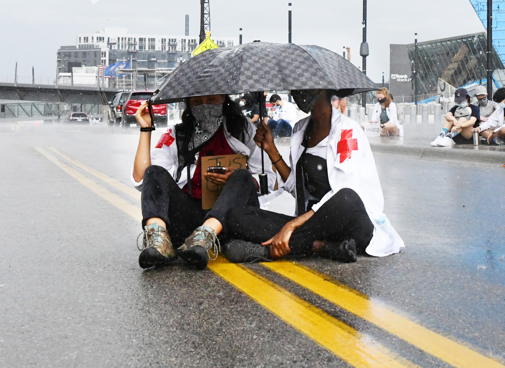University of Minnesota medical student Edith Hernandez times out eight minutes and forty-six seconds while leading a moment of silence as first-year medical student Safa Abdulkadir holds an umbrella over them in pouring rain outside of the Hennepin County Medical Examiner's office on Tuesday, June 2.