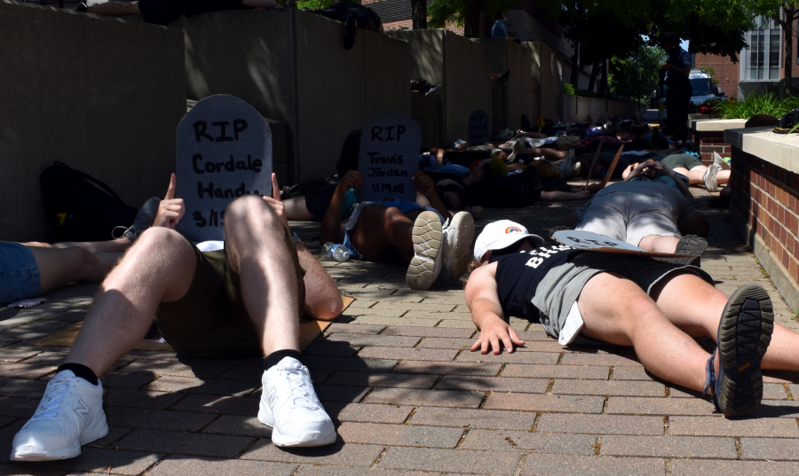 """Protesters hold up signs outside of University of Minnesota Police Department headquarters as part of a """"die-in"""" demanding the University disarm and defund UMPD on Sunday, June 7. They laid on the ground for eight minutes and 46 seconds to honor George Floyd."""
