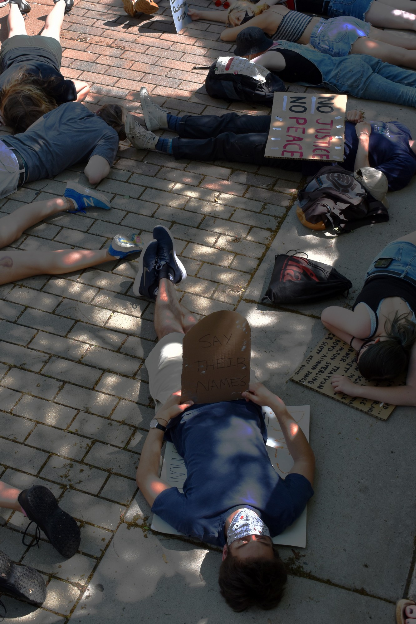 """Protesters lay on the ground outside of University of Minnesota Police Department headquarters as part of a """"die-in"""" demanding the University disarm and defund UMPD on Sunday, June 7. They laid on the ground for eight minutes and 46 seconds to honor George Floyd."""