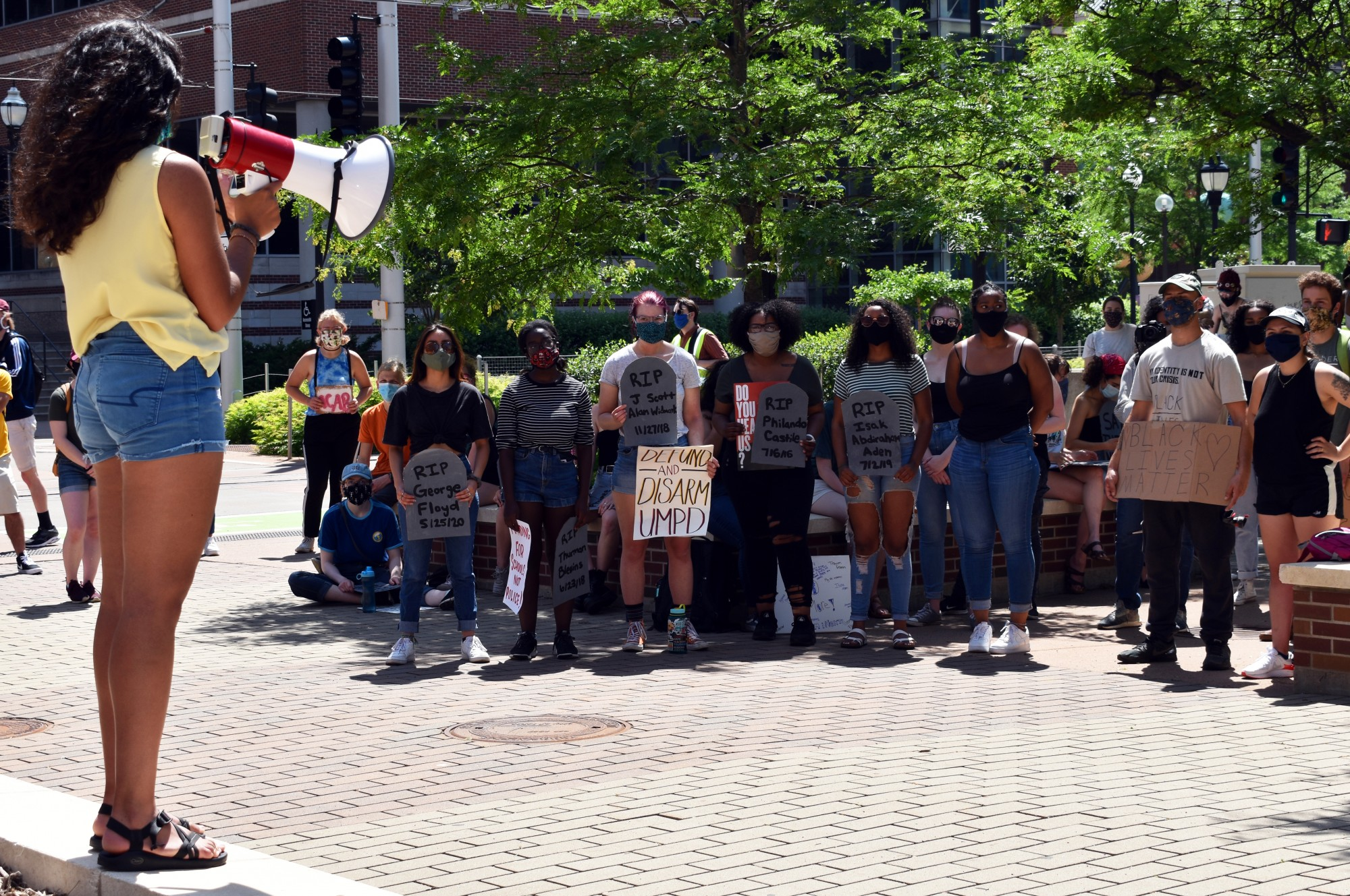 """Recent University of Minnesota graduate Natasha Sohni speaks to a group of about protesters outside of University of Minnesota Police headquarters as part of a """"die-in"""" demanding the University disarm and defund UMPD on Sunday, June 7."""