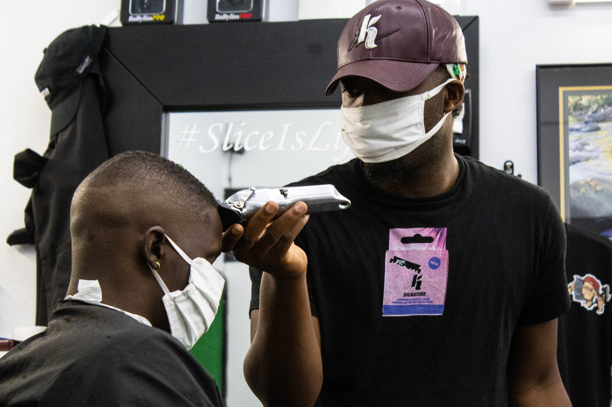 Mohammed Aliyu styles a customer's hair inside of K Signature Slice on Lake Street in Minneapolis on Monday, July 13.