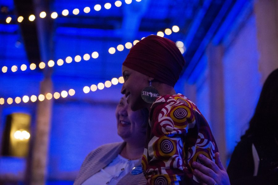 """Congresswoman Ilhan Omar hugs an attendee as their photo is being taken at Ilhan Omar 2020 Reelection Kickoff: """"Send Her Back to Congress"""" at Aria on Thursday, Jan. 23. (Nur B. Adam / Minnesota Daily)"""