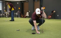 Thomas Longbella lines up a shot on the putting green in the indoor golf training facility in April 2019. The facility borders the Les Bolstad Golf Course and allows for practice throughout winter months.