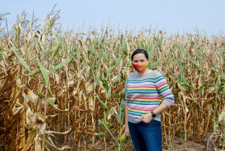 Climate Science Professor and Extension Specialist Heidi Roop poses near a field of corn on the University