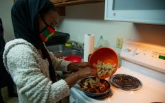 Oromo Student Union member Zubeda Chaffe cooks Caccabasa at the Keeler Apartments on Saturday, Oct. 24. Chaffe is combining bread with a sauce made of butter and spices.