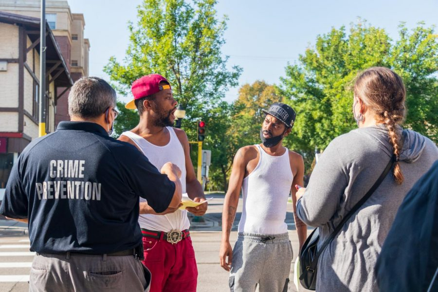 Lance King, middle left, and Darcell Jackson, middle right, react to information about recent criminal activity on Thursday, Sep. 24 in Dinkytown. Second Precinct Crime Prevention Specialist Nick Juarez, left, led the neighborhood safety walk to hand out flyers outlining current activity and tips to stay safe and alert.