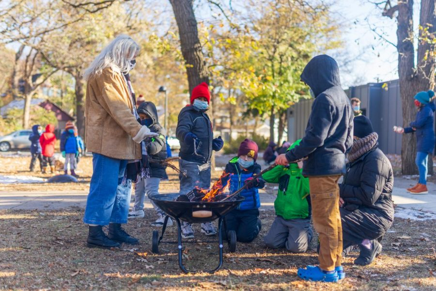 Participants in an after school program congregate around a fire at Luxton Park on Tuesday, Oct. 27th. The program was created to raise money for additional teachers and increase social time for students who