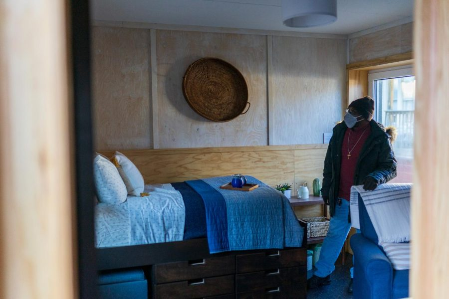 Freddy Toran walks into the living room of a tiny home outside Elm church on Wednesday, Dec. 9.