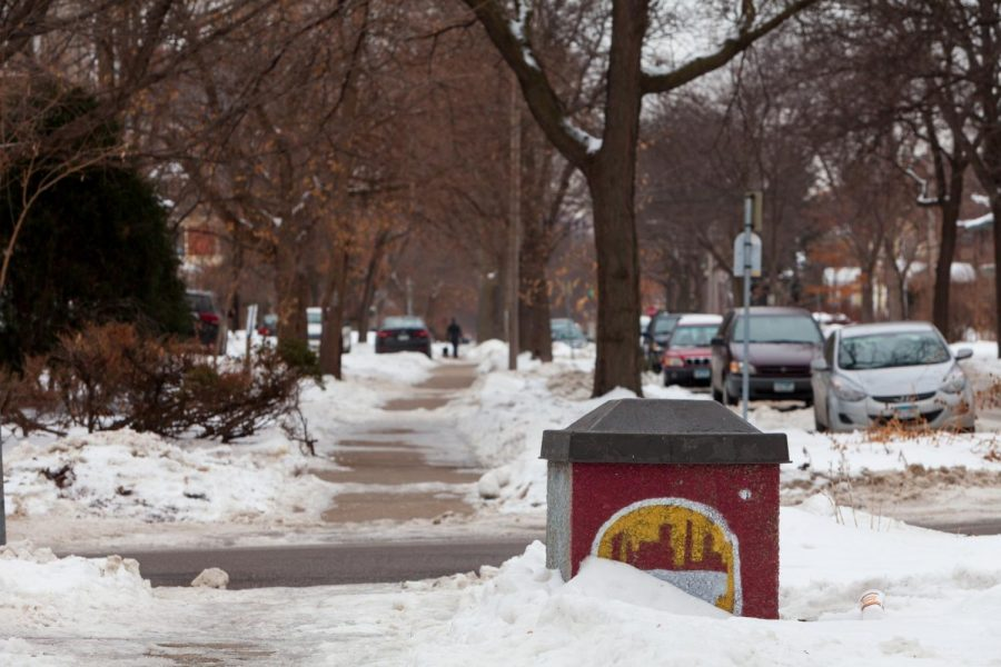 A trash bin adorned with the silhouette of Minneapolis is half buried in snow in the Marcy Holmes neighborhood on Tuesday, Jan. 28. The neighborhood provides housing for a significant number of University students.