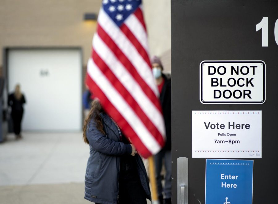 A voter waits in line to cast their ballot outside Marcy Open Elementary School on Tuesday, Nov. 3.