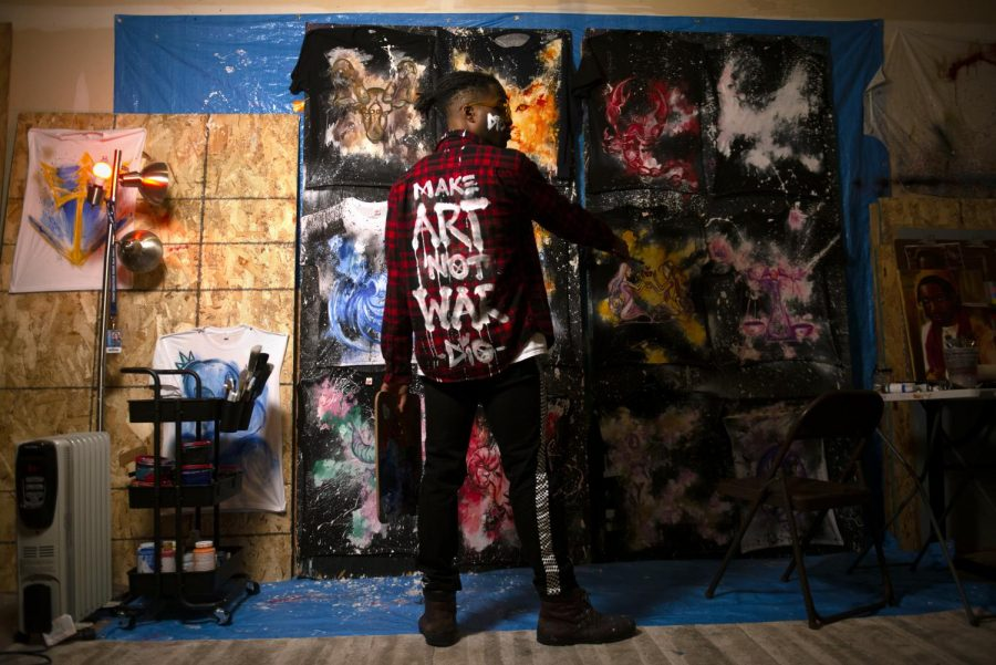 """Acting student and artist Nnamdi Darlington poses for a portrait in his studio in front of his artwork in Como on Tuesday, Dec. 1. """"I'm so grateful because I've really learned how to love where you come from,"""" said Darlington, a Twin Cities artist. """"At the end of the day, it's the place that has shaped you and molded you into who you are, and you can't remove that. You can't separate the environment from the experience."""""""