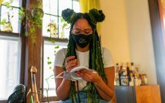 """Elizabeth Abraha stitches a new mask at her home on Monday, Nov. 30. """"I've always been a creative person, and now this is my way of making my thoughts real."""""""