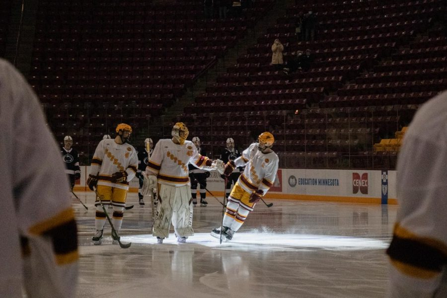 Gophers defenseman Jackson LaCombe fist bumps goaltender Jack LaFontaine during player introductions before facing Penn State at the 3M Arena at Mariucci on Thursday, Nov. 19.