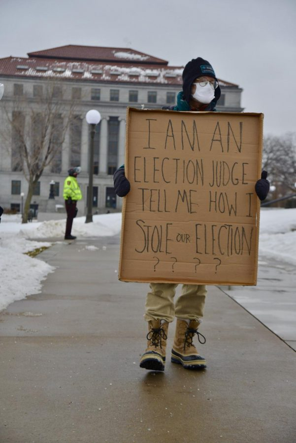 Election judge Steve Brandt holds a sign during the Hold the Line protest at the Minnesota Capitol on Saturday, Jan. 16. The event was held to protest the presidential election results.