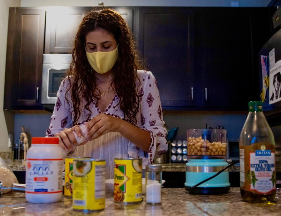 Nadia Aruri peels garlic cloves while making Hummus in her apartment on Friday, Jan. 15 in Minneapolis. Aruri is the Outreach Coordinator at University of Minnesota's student group Students for Justice in Palestine.