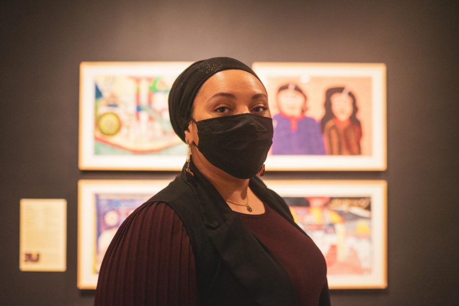 """Starasea Nidiala Camara poses for a portrait in front of the exhibition she curated at the Minneapolis Institute of Art on Thursday, Jan. 28. The exhibition features African American artists, centering the work of artists from the """"Black Belt"""" region of the South."""