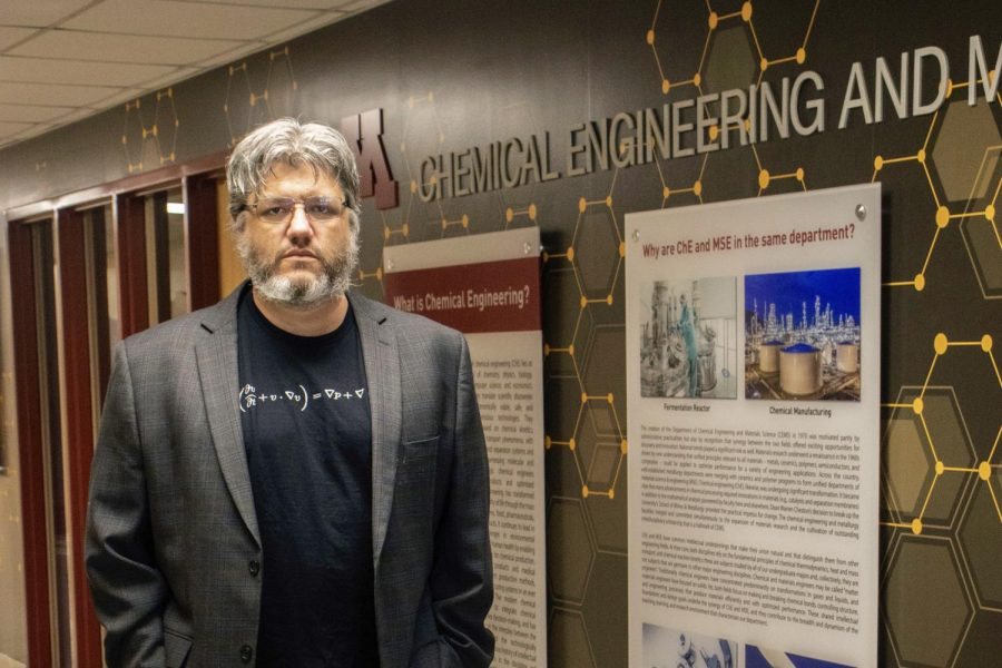 Chemical engineering researcher Dr. Paul Dauenhauer poses for a portrait in front of a new chemical engineering and materials science display in Amundson Hall on Saturday, Feb. 13. Dauenhauer leads a lab that is developing biodegradable technologies to become an alternative to plastic and rubber.