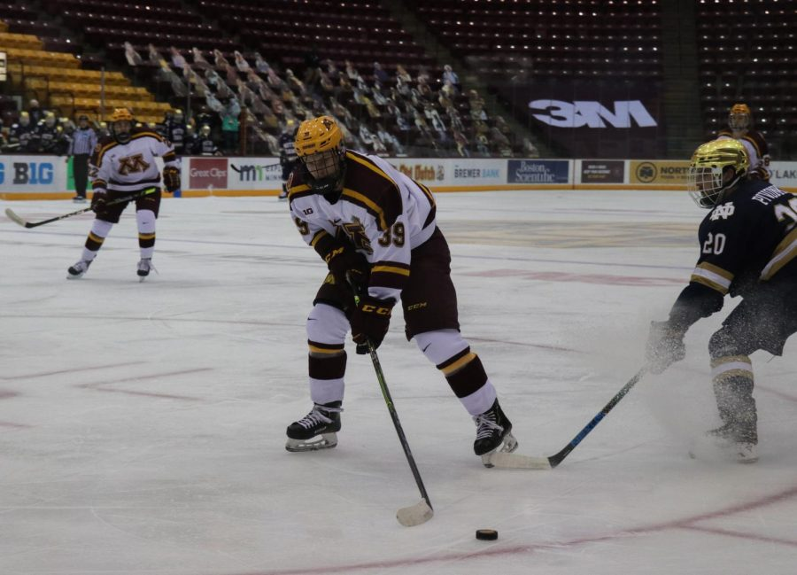 Gopher's Ben Meyers skates past Notre Dame's Jake Pivonka toward Notre Dame's goal in the first period of the match on Saturday, Jan. 19 at the 3M Arena at Mariucci.