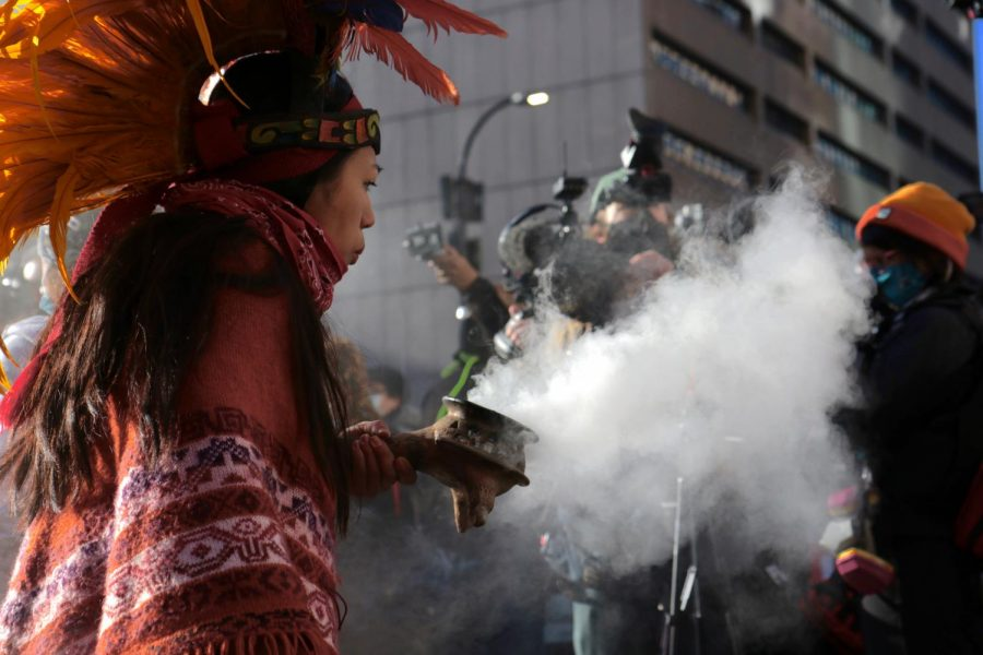 An Aztec Indigenous dance group member blows smoke in a performance as part of a protest outside of Hennepin County Government Center on Monday, March 8. A coalition of activist groups organized the protest for the first scheduled day of Derek Chauvin's trial.