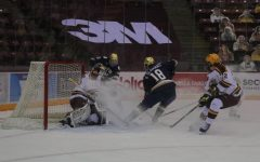 Minnesota's goalie Jack LaFontaine blocks an attempted goal from Notre Dame's Graham Slaggert on Saturday, Jan. 16 at the 3M arena at Marriucci.