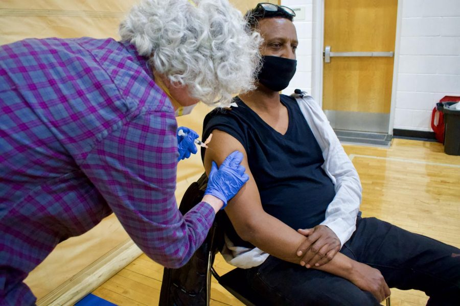 Nurse Carol Gilbert administers a COVID-19 vaccine to Rep. Ilhan Omar's Deputy District Director Ali Isse at the Brian Coyle Center on Friday, March 12. The Brian Coyle Center has started offering COVID-19 vaccinations on Fridays from 1 p.m. to 4 p.m.