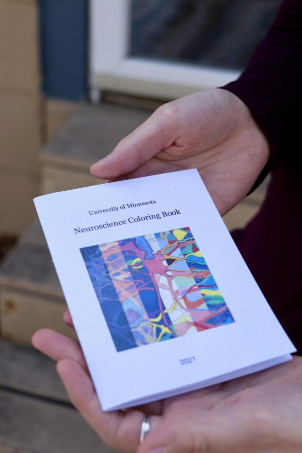 Samantha Montoya holds the neuroscience coloring book she created on Monday, Mar. 8.  The book includes DNA binding domain structures, heat shock transcription, and more.