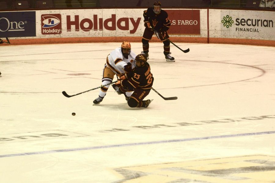 Forward Nathan Burke blocks Arizona State's Justin Robbins from reaching the puck in 3M Arena on Friday, Jan. 22. The Gophers beat Arizona State with a final score of 10-2.