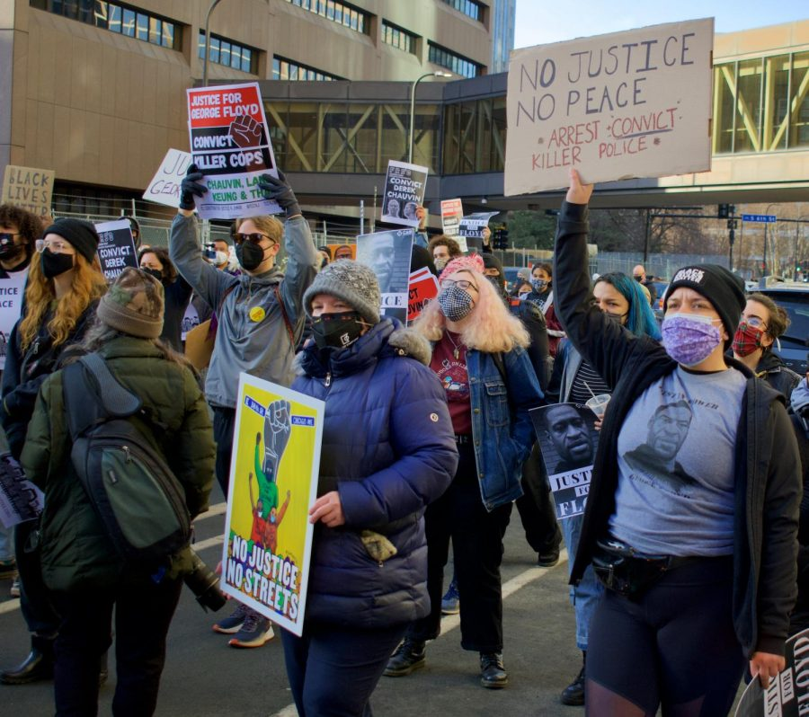 Protesters march by Hennepin County Government Center as part of the Justice for George Floyd protest on Monday, March 8. A coalition of activist groups organized the protest for the first scheduled day of Derek Chauvin's trial.