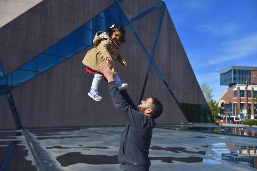 3:57 p.m. Father Saab Malik plays with his daughter, Aylah Malik, in front of McNamara Alumni Center. Saab Malik and his daughter were waiting for his wife, who lives near campus.
